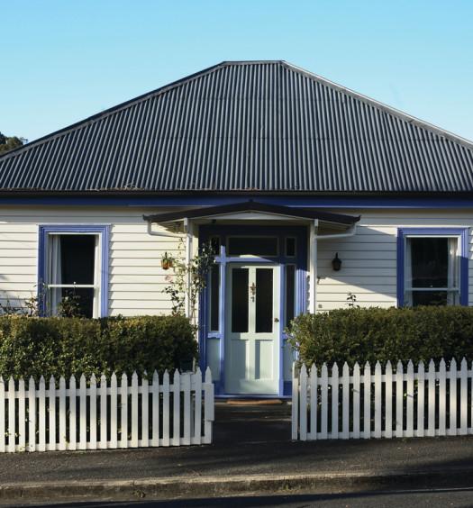 Maison blanc et bleue avec cloture
