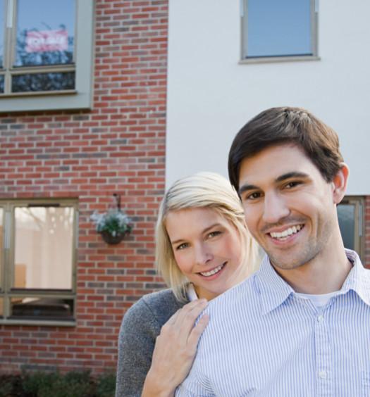 Couple posant devant immeuble en brique