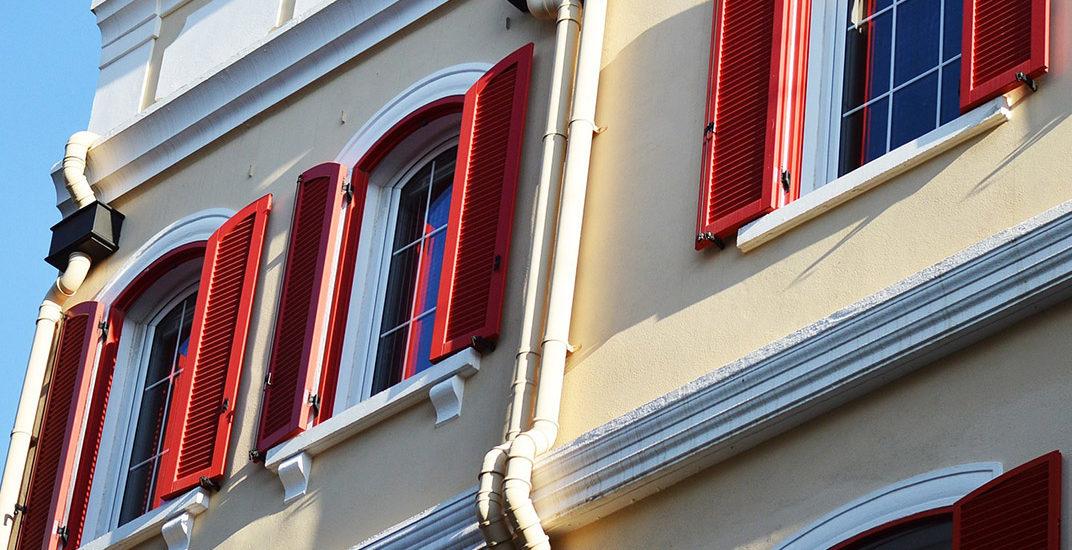 Façade de maison aux volets rouge